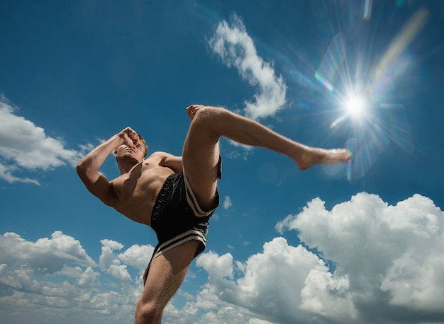 Kickboxer calcia all'aria aperta in estate contro il mare.