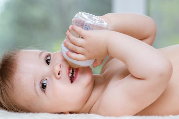 Kid beve una composta da una bottiglia a casa