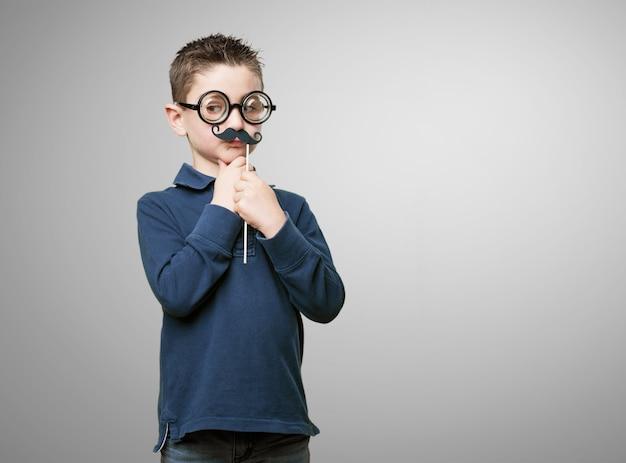 Kid con gli occhiali e baffi finti
