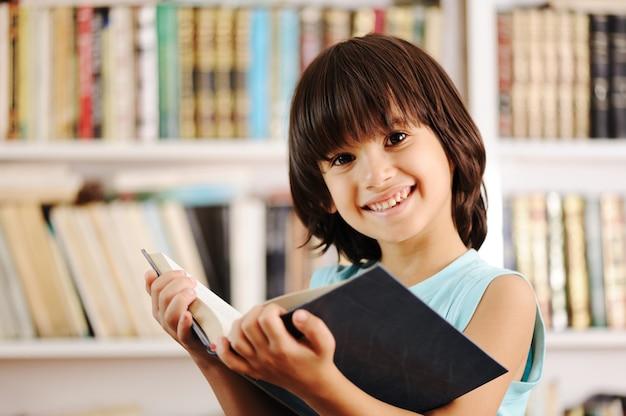 Kid con il libro in biblioteca