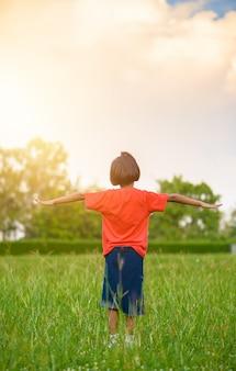 Kid in piedi e allungare le braccia o estendere le braccia nei campi di erba