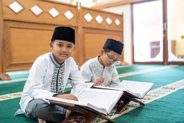 Kid musulmano leggendo il corano
