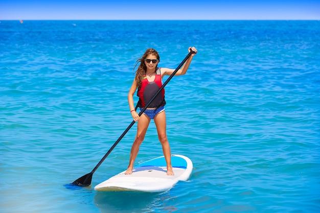 Kid paddle surf surfer ragazza con fila in spiaggia