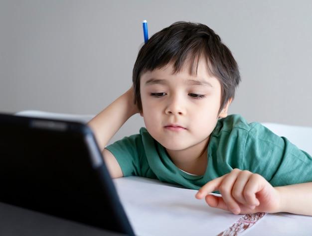 Kid stare a casa a guardare cartoni animati su teblet, bambino utilizzando la tavoletta digitale alla ricerca di informazioni su internet per i suoi compiti. distanziamento sociale, apprendimento dell'istruzione online