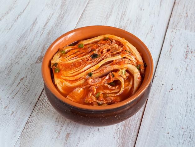 Kimchi coreano da cavolo cinese su una tavola di legno bianca.
