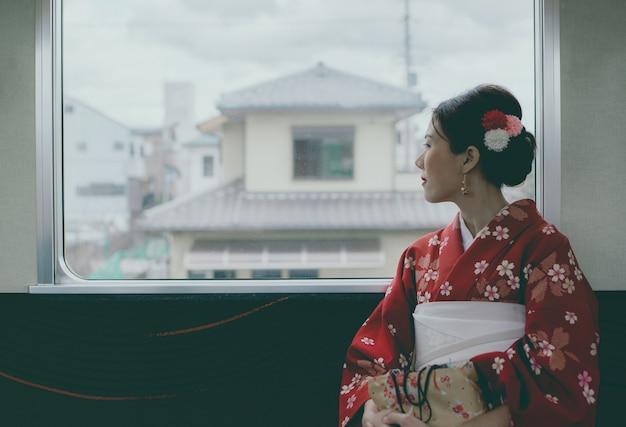 Kimono d'uso della donna asiatica che viaggia in treno classico del giappone che si siede vicino alla finestra