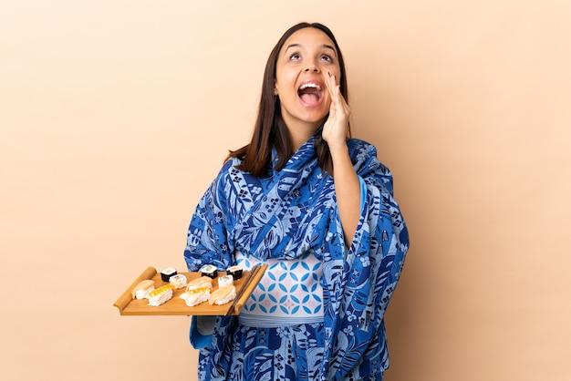 Kimono d'uso della donna e tenere i sushi sopra gridare isolato e annunciare qualcosa