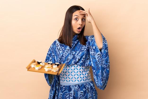Kimono d'uso della donna e tenere i sushi sopra il gesto di sorpresa facente isolato mentre guardando la parte anteriore