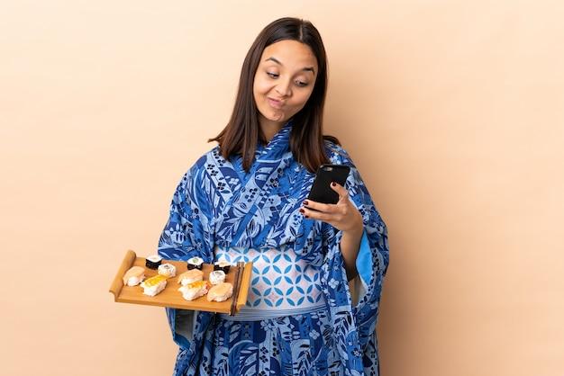 Kimono d'uso della donna e tenere i sushi sopra il pensiero isolato e l'invio del messaggio