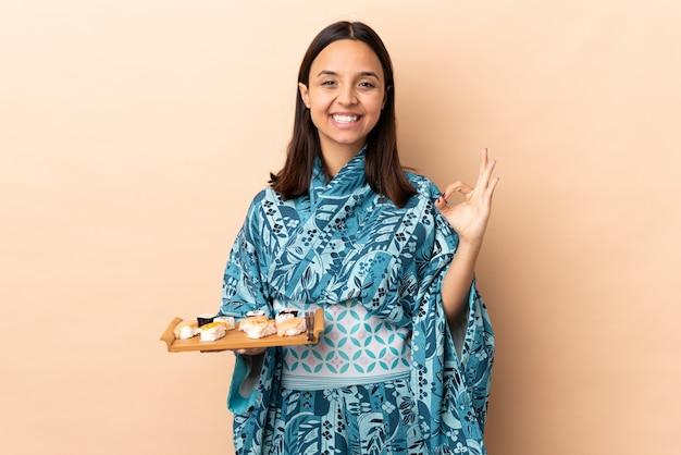 Kimono d'uso della donna e tenere i sushi sopra il segno giusto di mostra isolato con due mani