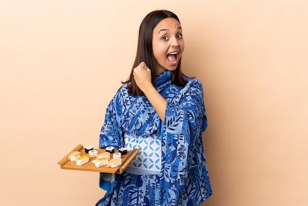 Kimono d'uso della donna e tenere i sushi sopra isolati celebrando una vittoria