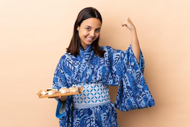 Kimono d'uso della donna e tenere i sushi sopra la parete che fa forte gesto