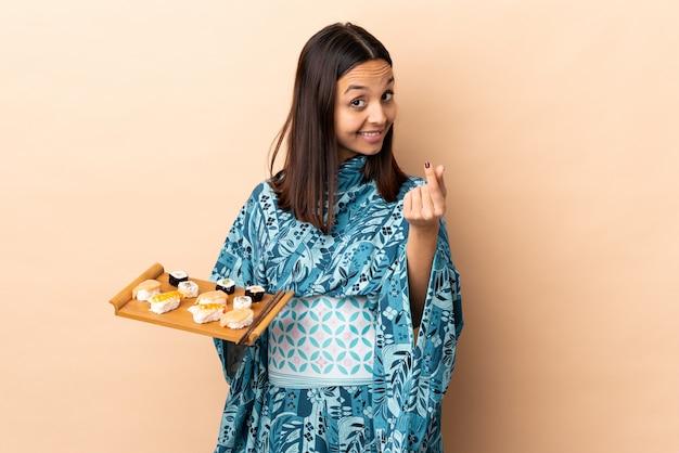 Kimono d'uso della donna e tenere i sushi sopra la parete che fa gesto dei soldi