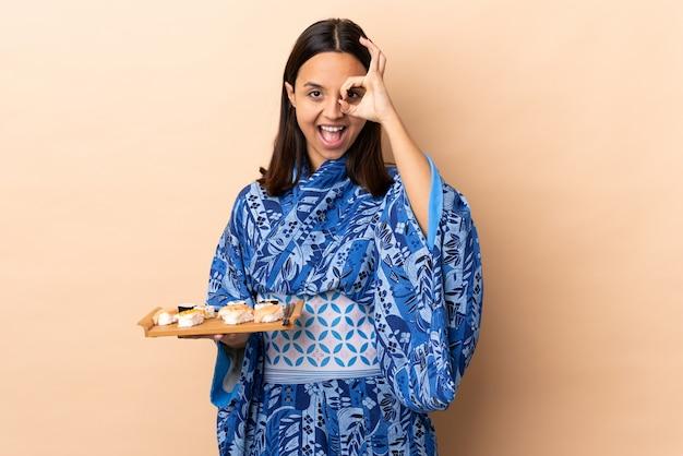 Kimono d'uso della donna e tenere i sushi sopra la parete che mostra segno giusto con le dita