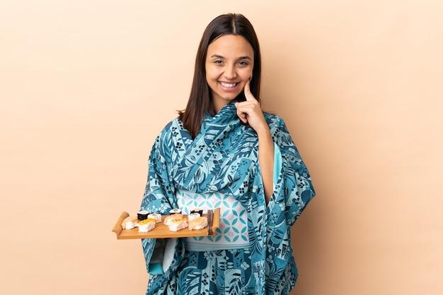 Kimono d'uso della donna e tenere i sushi sopra la parete che sorride con un'espressione felice e piacevole
