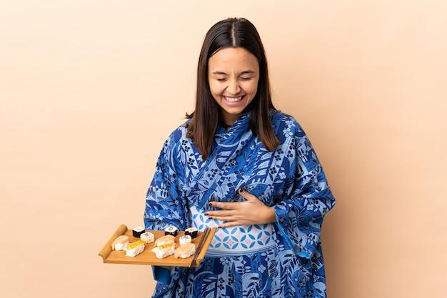 Kimono d'uso della donna e tenere i sushi sopra la parete che sorridono molto