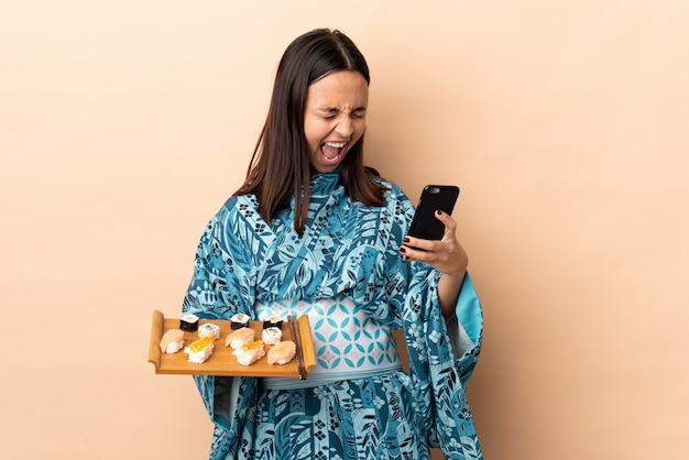 Kimono d'uso della donna e tenere i sushi sopra la parete con il telefono nella posizione di vittoria