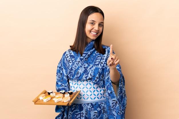 Kimono d'uso della donna e tenere i sushi sopra la rappresentazione della parete e sollevare un dito