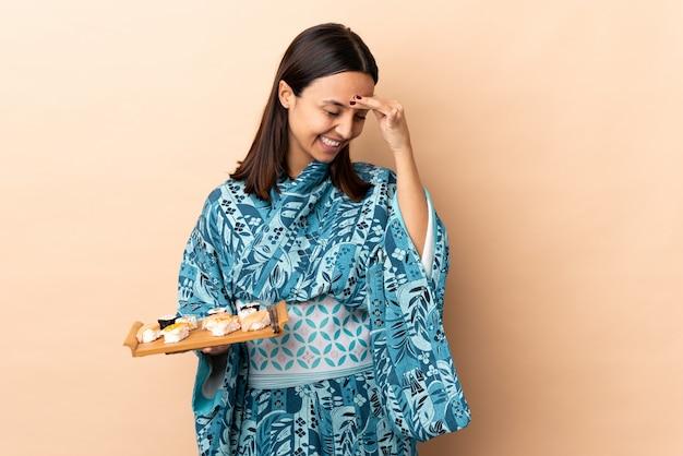 Kimono d'uso della donna e tenere i sushi sopra la risata della parete