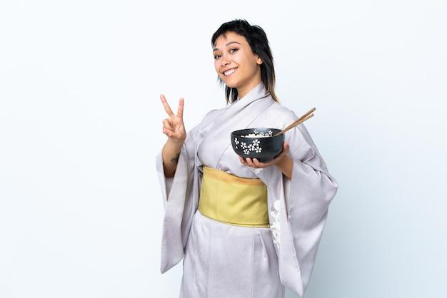 Kimono d'uso della giovane donna che tiene una ciotola di tagliatelle sopra la parete bianca che sorride e che mostra il segno di vittoria