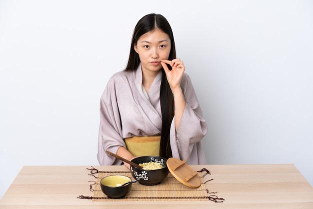 Kimono d'uso della giovane donna cinese e mangiare le tagliatelle che mostrano un segno di gesto di silenzio