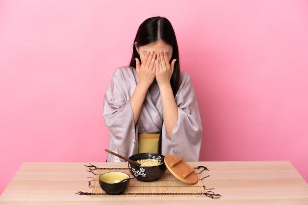 Kimono d'uso della giovane donna cinese e mangiare le tagliatelle con l'espressione stanca e malata
