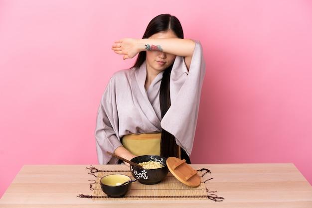 Kimono d'uso della giovane ragazza cinese e mangiare le tagliatelle che coprono gli occhi a mano