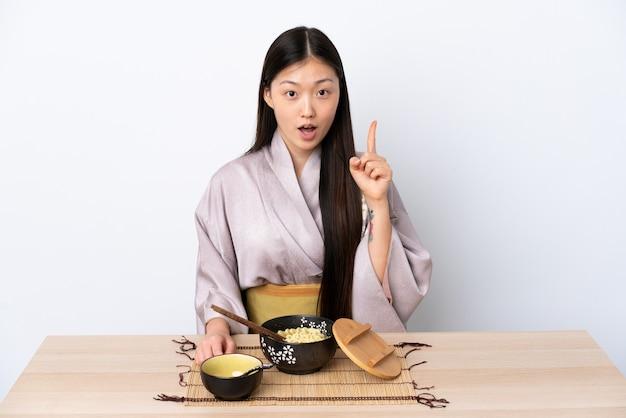 Kimono d'uso della giovane ragazza cinese e mangiare le tagliatelle che pensano un'idea che indica il dito su