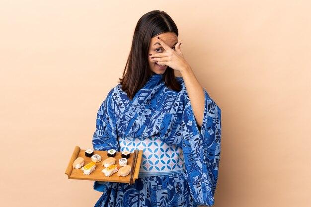 Kimono da portare della donna e tenere i sushi sopra il rivestimento della parete osserva a mano e sorridendo