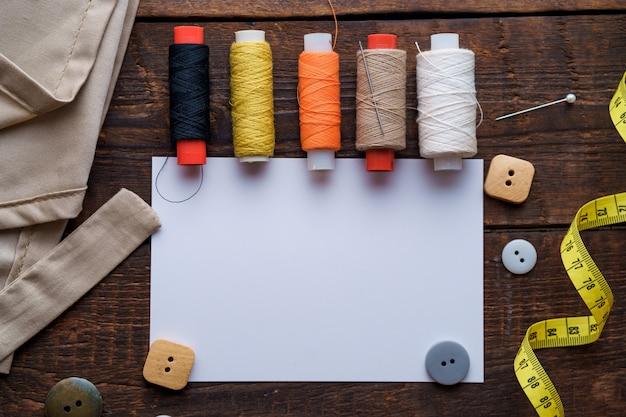 Kit da cucito e vari materiali di consumo per cucire per sarta su fondo di legno scuro. vista dall'alto. copia spazio