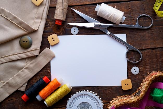 Kit da cucito e vari materiali di consumo per cucito per sarta su fondo di legno scuro