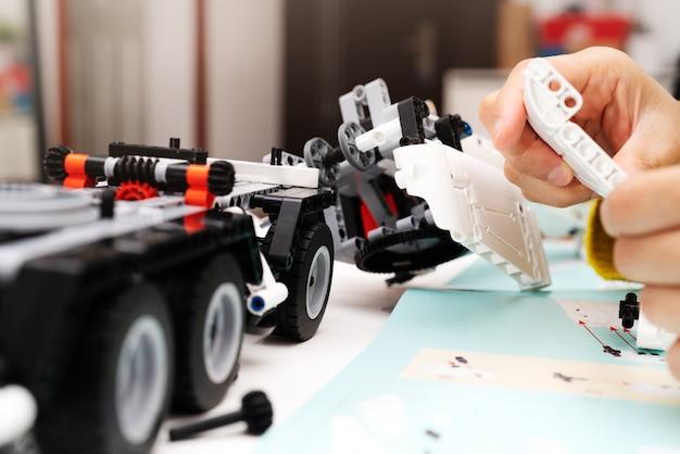 Kit di montaggio per auto, la donna assembla un giocattolo di camion per auto molto complicato e comune.