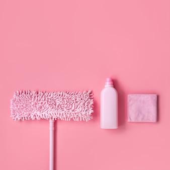 Kit di pulizia in casa rosa su uno sfondo rosa