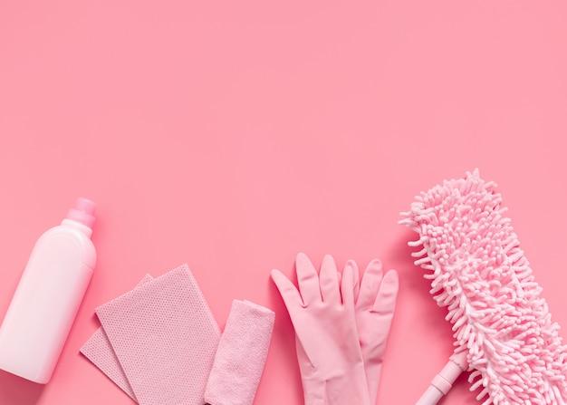 Kit di pulizia in casa rosa su uno sfondo rosa.