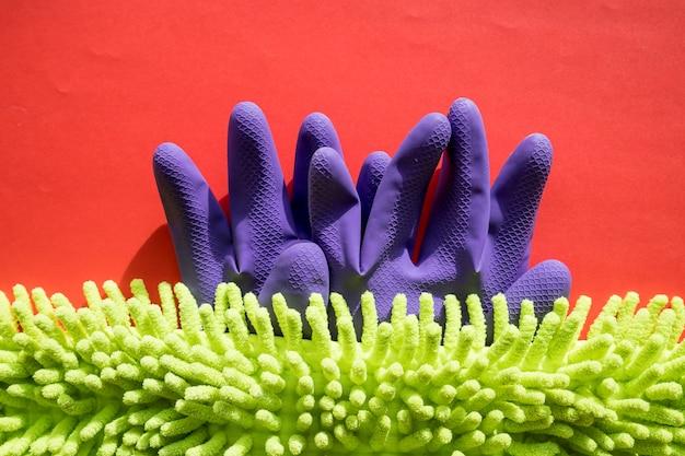Kit di pulizia isolato sulla parete rossa. set di tovaglioli, guanti di gomma e spugne. kit professionale per la pulizia della casa. composizione degli strumenti di pulizia.