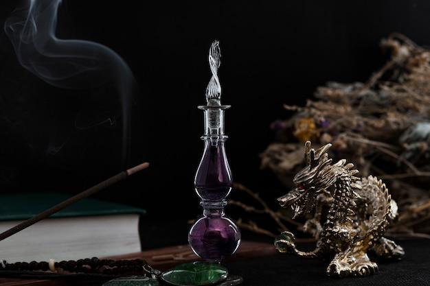Kit strega. al centro c'è una bottiglia a forma di viola con una pozione. a destra è un drago d'oro, a sinistra è un bastoncino di incenso e un libro.