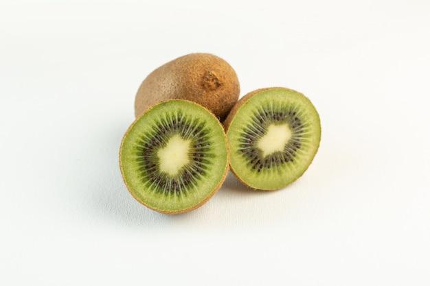 Kiwi acidi marroni affettati allineati isolati sulla superficie bianca