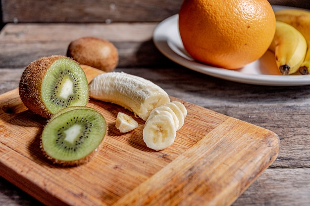 Kiwi e banana affettati sul bordo della cucina sui precedenti del pompelmo e delle banane in un piatto. cucinare la macedonia nella cucina di casa.
