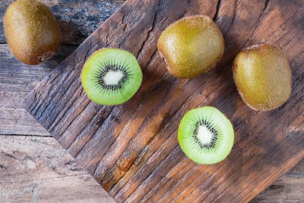 Kiwi fresco tagliato a metà su un tagliere di legno.
