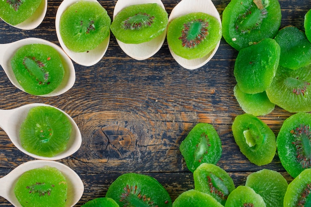 Kiwi secchi fette in cucchiai su sfondo di legno, piatto laici.