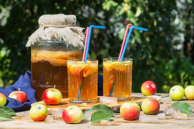 Kombucha bere in un barattolo di vetro e un bicchiere con cannucce rosa e blu, mele fermentate, nel giardino estivo, su un tavolo di legno. stile rustico