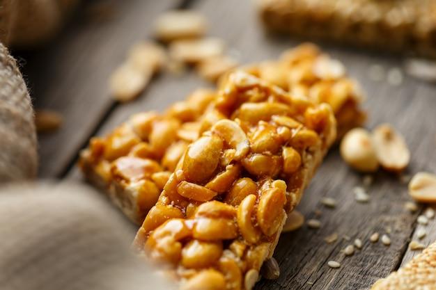 Kozinaki assortiti ,, con tessuto di juta. stile country. deliziosi dolci dai semi di girasole, sesamo e arachidi, ricoperti di glassa lucida.