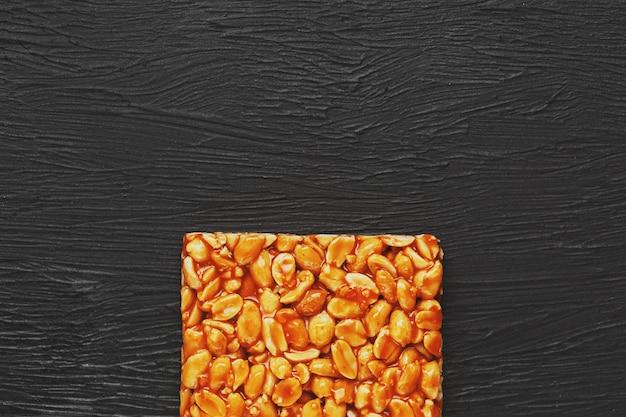 Kozinaki di boletus dorato da barrette energetiche di fagioli di arachidi tostate. sfondo nero strutturale, vista dall'alto