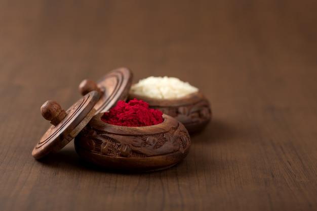 Kumkum e contenitore per chicchi di riso. le polveri di colore naturale vengono utilizzate durante l'adorazione di dio e in occasioni propizie.