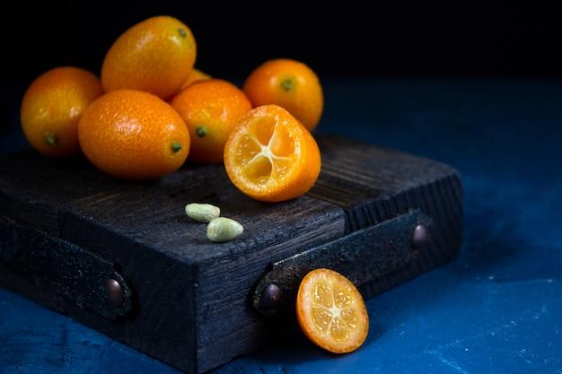 Kumquat fresco su una parete scura