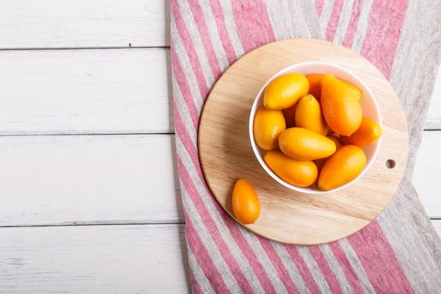 Kumquat in un piatto bianco su un bianco in legno
