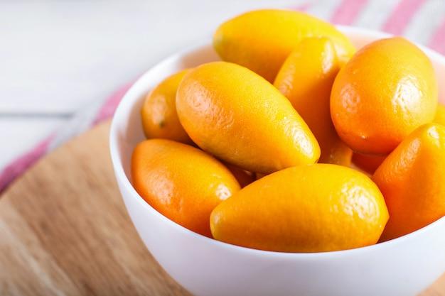 Kumquat in un piatto bianco su un fondo di legno bianco