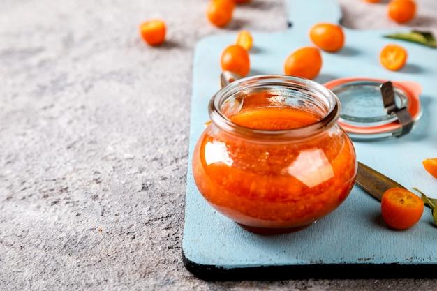 Kumquat jam sulla superficie grigia. bright citrus.c