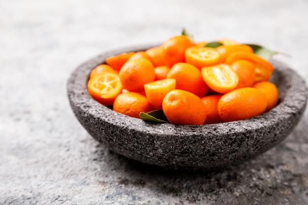 Kumquat sulla superficie grigia. agrumi luminosi.