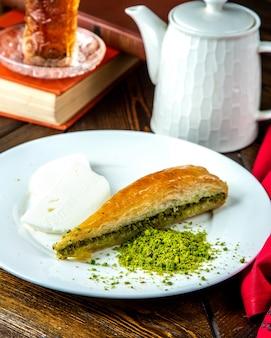 Kunefe turco del dessert con la vista laterale dei pistacchi del gelato
